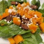 bed of spinach on plate topped with butternut squash, pecans and goat cheese