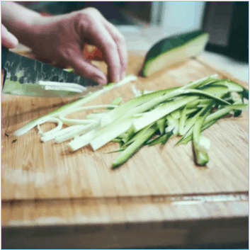 wood chopping board with hands chopping fresh zucchini into strips