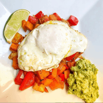 plate of sweet potato hash topped with over easy egg and a side of mashed avocado and lime wedge