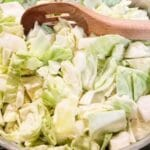picture of raw chopped cabbage in pan with wooden spoon