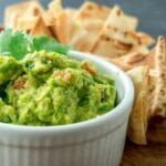 Picture of guacamole in white bowl with chips