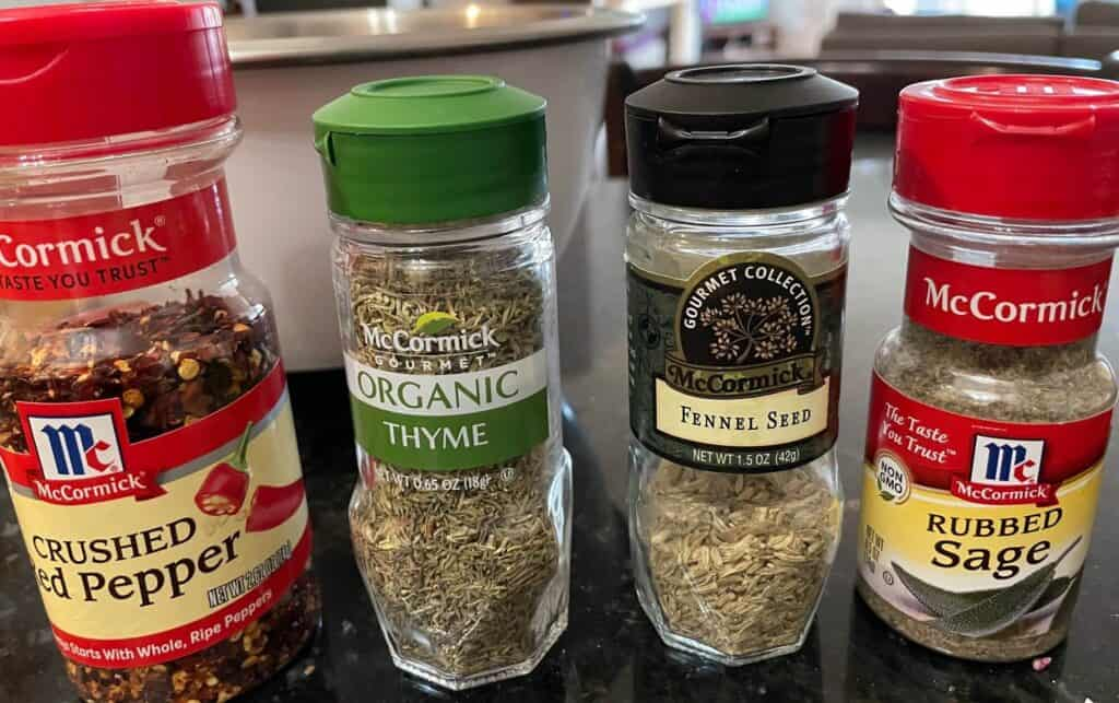 Picture of spice bottles used in low sodium sausage recipe: crushed red pepper, thyme, fennel and sage.