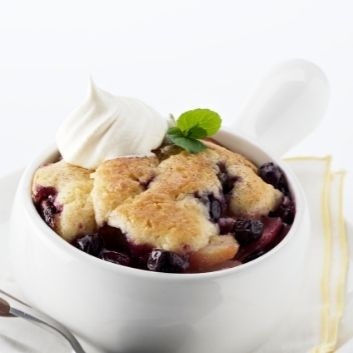 Fresh blueberry cobbler in a white serving dish topped with whipped cream and mint leaves