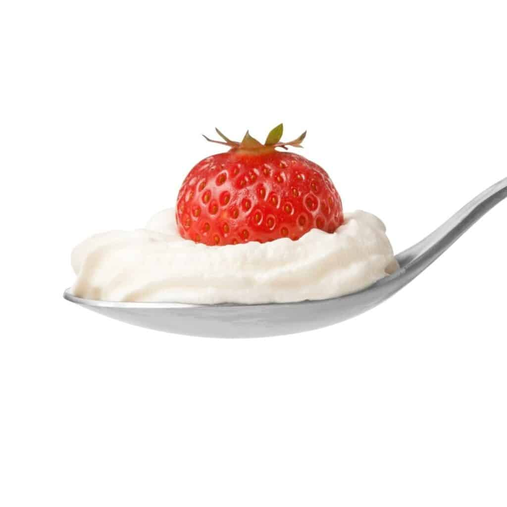 spoon with whipped cream and a strawberry